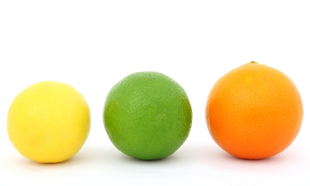 a yellow lemon, a green lime and an red coloured orange