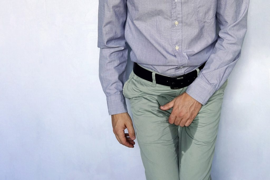 man with hands holding his crotch on a light blue background. Urinary incontinence.