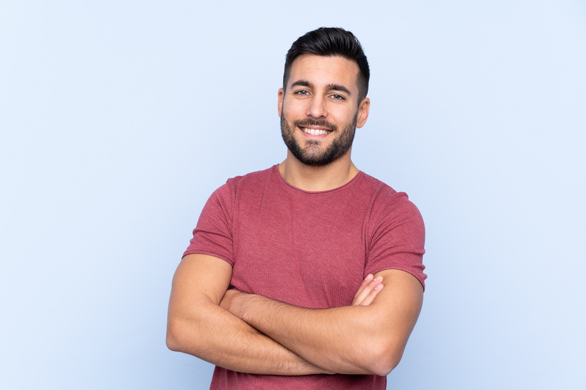 Young handsome man with beard over isolated blue background